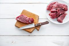 Ruw vlees Ruw vers rundvleeslapje vlees op een houten scherp raad en een Voorsnijmes Witte houten achtergrond, hoogste mening, ex royalty-vrije stock afbeeldingen