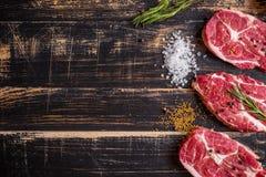 Ruw vleeslapje vlees op donkere houten achtergrond klaar aan het roosteren Royalty-vrije Stock Foto