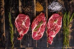 Ruw vleeslapje vlees op donkere houten achtergrond klaar aan het roosteren Stock Fotografie