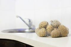 Ruwe aardappels in een zak bij keukenlijst Stock Foto's