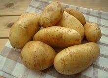 Ruwe aardappels op de keukenhanddoek, rustieke stijl Stock Foto