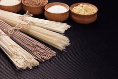 Ruwe Aziatische noedels met ingrediënt in houten kommen op zwarte gestreepte matachtergrond met exemplaarruimte Royalty-vrije Stock Foto