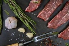 Ruwe biefstuk met kruiden, zwarte achtergrond, hoogste mening stock afbeeldingen