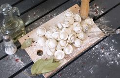 Ruwe bollen in bloem op een scherpe Raad, hoogste mening, Corolla, laurierblad, olie in een fles, zout in een zoute schudbeker royalty-vrije stock foto's
