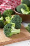 Ruwe broccoli op scherpe raad en kom op een lijst Royalty-vrije Stock Afbeeldingen