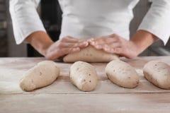 Ruwe broden van brood op lijst en de mens Stock Foto's