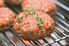 Ruwe burgers bij bbq de barbecuegrill met brand Royalty-vrije Stock Fotografie
