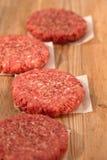 Ruwe burgers voor hamburgers, op houten lijst stock afbeelding