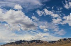 Ruwe dessertheuvels in de afstand onder een reusachtige fantastically blauwe hemel met mooie pluizige witte wolken Royalty-vrije Stock Foto's