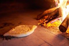 Ruwe die Ajarian-khachapuri in een oven met het branden van brandhout wordt gekookt stock fotografie