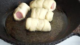 Ruwe die hotdogs op de pan voor het koken worden opgemaakt stock footage