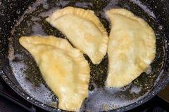 Ruwe die pasteien met vlees in een pan in zonnebloemolie wordt gebraden stock afbeelding
