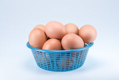 Ruwe eieren in blauwe mand op witte achtergrond Stock Foto's