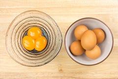Ruwe eieren in ceramische kom en eierdooiers in glazenkom Royalty-vrije Stock Fotografie