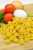 Ruwe en verse macaroni, tomaten, ei en ui stock afbeeldingen