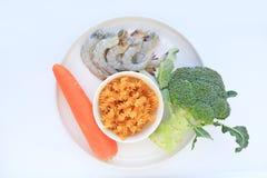 Ruwe Garnalen met macaroni en groente op witte plaat tegen witte achtergrond royalty-vrije stock afbeelding