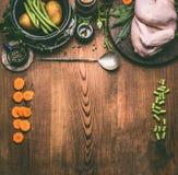 Ruwe gehele kip op de rustieke houten achtergrond van de keukenlijst met groenteningrediënten en lepel stock afbeelding