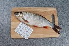 Ruwe gekookte niet vissen, Witte vissen op een knipselraad en pillen royalty-vrije stock foto