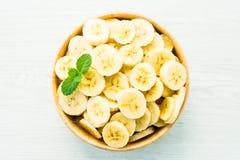 Ruwe gele banaanplakken in houten kom Stock Foto's