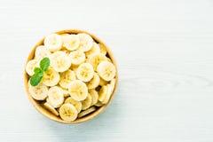 Ruwe gele banaanplakken in houten kom Stock Afbeeldingen