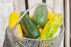 Ruwe gele en groene courgette in rieten mand stock afbeelding