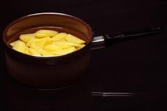 Ruwe gepelde aardappels in pottenpan op zwarte. Gezond voedsel. Stock Afbeeldingen