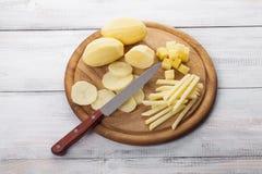 Ruwe gepelde en gesneden aardappels op scherpe raad Royalty-vrije Stock Foto's