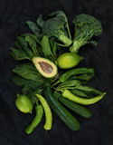 Ruwe groene geplaatste groenten Broccoli, avocado, peper, spinazie, courgette, kalk op donkere steenachtergrond Royalty-vrije Stock Foto's