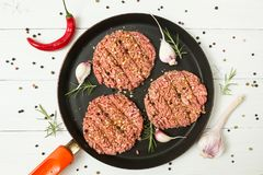 Ruwe hamburgers - gehakt van organisch vlees met kruidnagels van knoflook, hete Spaanse peperpeper en rozemarijn in een pan op ee royalty-vrije stock afbeeldingen