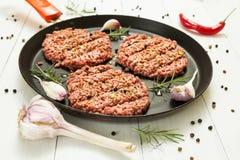 Ruwe hamburgers - koteletten van organisch rundvleesvlees met knoflook, Spaanse pepers en rozemarijn in een pan op een witte acht stock foto