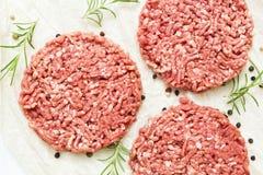 Ruwe hamburgers zonder vet van organisch rundvlees op een witte houten achtergrond met kruiden Voedend voedsel Hoogste mening stock afbeeldingen