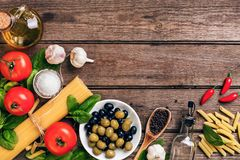 Ruwe ingrediënten voor de voorbereiding van Italiaanse deegwaren, spaghetti, basilicum, tomaten, olijven en olijfolie op houten Stock Foto's