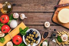 Ruwe ingrediënten voor de voorbereiding van Italiaanse deegwaren, spaghetti, basilicum, tomaten, olijven en olijfolie op houten Royalty-vrije Stock Foto's