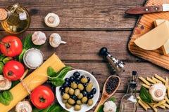 Ruwe ingrediënten voor de voorbereiding van Italiaanse deegwaren, spaghetti, basilicum, tomaten, olijven en olijfolie op houten Royalty-vrije Stock Fotografie