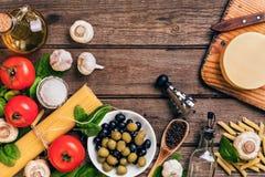 Ruwe ingrediënten voor de voorbereiding van Italiaanse deegwaren, spaghetti, basilicum, tomaten, olijven en olijfolie op houten Stock Afbeeldingen