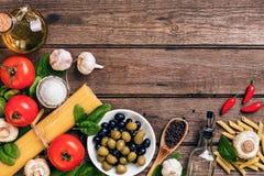 Ruwe ingrediënten voor de voorbereiding van Italiaanse deegwaren, spaghetti, basilicum, tomaten, olijven en olijfolie op houten Stock Foto