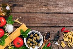 Ruwe ingrediënten voor de voorbereiding van Italiaanse deegwaren, spaghetti, basilicum, tomaten, olijven en olijfolie op houten Stock Afbeelding