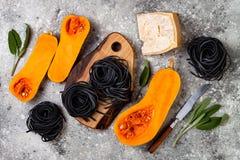 Ruwe ingrediënten voor het maken van zwarte deegwaren met butternut pletten, parmezaanse kaaskaas en salie Zwart en oranje de par Royalty-vrije Stock Afbeelding