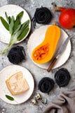 Ruwe ingrediënten voor het maken van zwarte deegwaren met butternut pletten, parmezaanse kaaskaas en salie Zwart en oranje de par Royalty-vrije Stock Foto's