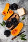 Ruwe ingrediënten voor het maken van zwarte deegwaren met butternut pletten, parmezaanse kaaskaas en salie Zwart en oranje de par Stock Afbeeldingen