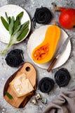 Ruwe ingrediënten voor het maken van zwarte deegwaren met butternut pletten, parmezaanse kaaskaas en salie Zwart en oranje de par Stock Foto