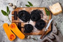 Ruwe ingrediënten voor het maken van zwarte deegwaren met butternut pletten, parmezaanse kaaskaas en salie Zwart en oranje de par Royalty-vrije Stock Foto