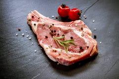 Ruwe kalfsvleeskotelet bij zwarte leiplaat Stock Afbeelding