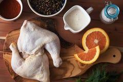 Ruwe kippenbenen en marinadeingrediënten op de houten raad royalty-vrije stock afbeelding