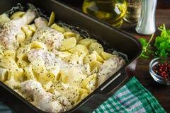 Ruwe kippenbenen met ruwe aardappels in mayonaise in de vorm voor baksel op een houten lijst Vleesingrediënten voor het koken rec Stock Afbeelding