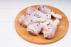 Ruwe kippenbenen met groene paprika op een cirkel houten raad  Royalty-vrije Stock Foto
