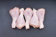 Ruwe kippenbenen met pepererwten op een grijze achtergrond Stock Afbeelding