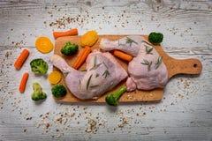 Ruwe kippenbenen van groenten aan een houten lijst Royalty-vrije Stock Afbeelding