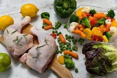 Ruwe kippenbenen van groenten aan een houten lijst Stock Afbeeldingen