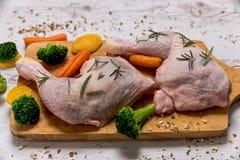 Ruwe kippenbenen van groenten aan een houten lijst Royalty-vrije Stock Afbeeldingen